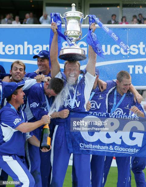Sussex captain Chris Adams lifts the trophy and gets a faceful of champagne from teammate Murray Goodwin after Sussex win the Cheltenham and...