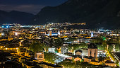 Sustainable city, colorful lights and traffic in mountain valley, Trento, Italy