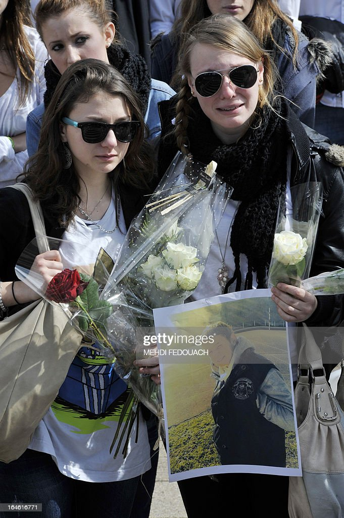 Susy (L), the girlfriend of Sylvain, a 15-year-old schoolboy stabbed on March 19 by a 19-year-old comrade in a classroom of the Estuaire college in Blaye, southwestern France, attends a march in his honour on March 25, 2013 in Blaye. AFP PHOTO MEHDI FEDOUACH.