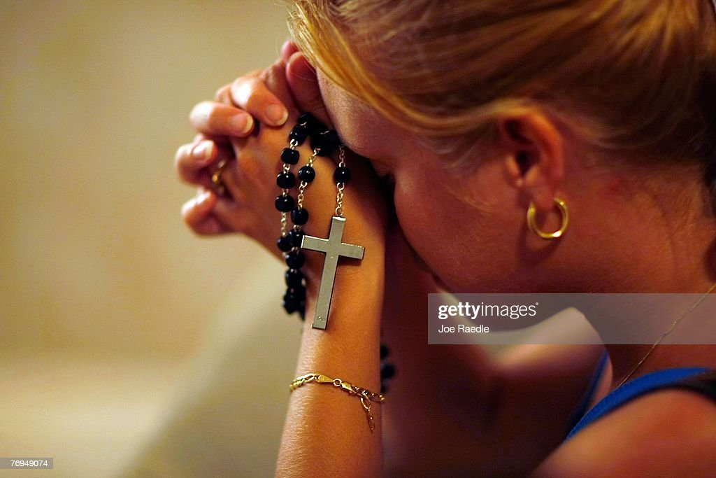 Susy Vazquez prays before a shadow that has formed what many think is the silhouette of the Holy Family Joseph and the Virgin Mary standing over the...