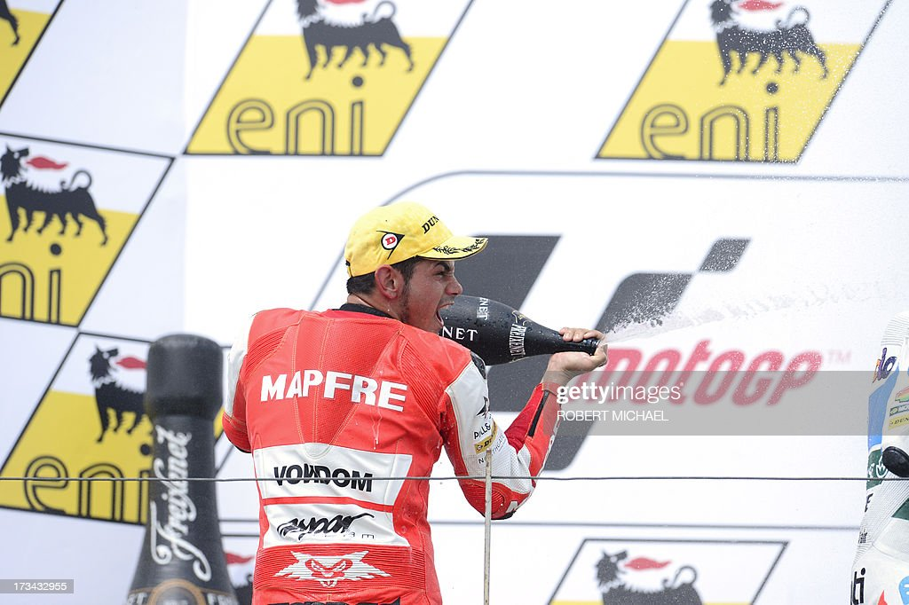Suter driver Jordi Torres of Spain celebrates his win on the podium after competing in the Moto2 race Grand Prix Germany at the Sachsenring Circuit on July 14, 2013 in Hohenstein-Ernstthal, eastern Germany. AFP PHOTO / ROBERT MICHAEL