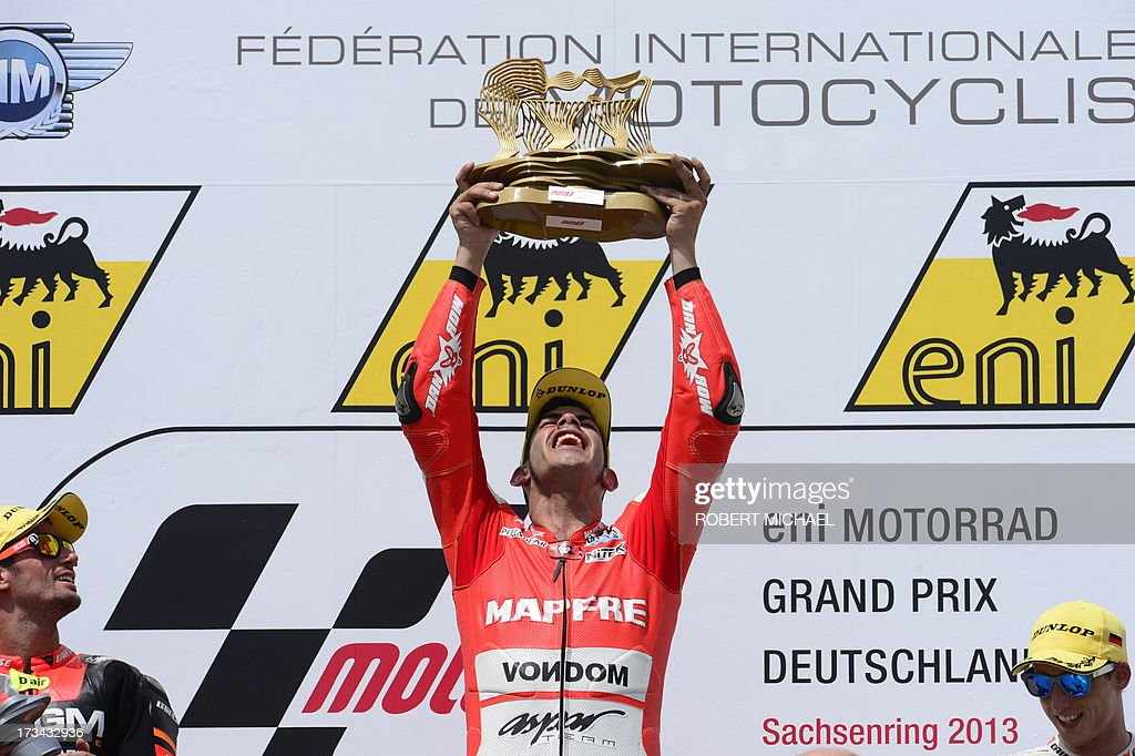 Suter driver Jordi Torres of Spain (C) holds up his trophy as he celebrates his win on the podium after competing in the Moto2 race Grand Prix Germany at the Sachsenring Circuit on July 14, 2013 in Hohenstein-Ernstthal, eastern Germany. AFP PHOTO / ROBERT MICHAEL