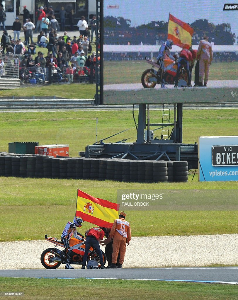 suter rider marc marquez of spain flies the spanish flag after his