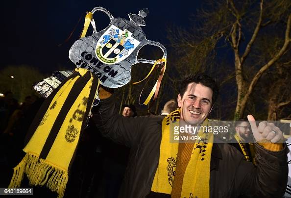 A Sutton fan arrives carrying a cutout FA Cup ahead of the English FA Cup fifth round football match between Sutton United and Arsenal at the Borough...