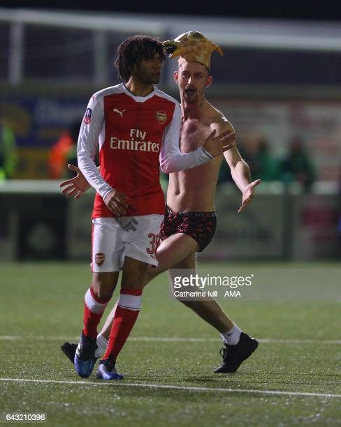 Sutton United fan wearing a giraffe hat runs onto the pitch behind Mohamed Elneny of Arsenal during The Emirates FA Cup Fifth Round match between...