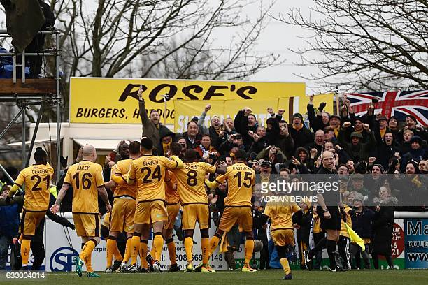 Sutton United's English defender Jamie Collins celebrates with teammates after scoring the opening goal from the penalty spot during the English FA...