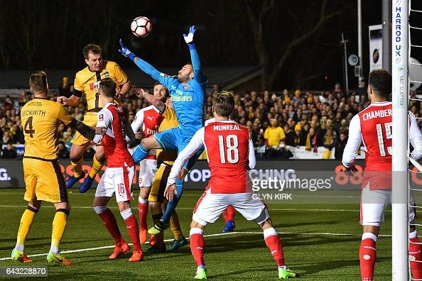 Sutton United's English defender Jamie Collins heads towards goal as Arsenal's Colombian goalkeeper David Ospina fails to claim but the attempt goes...