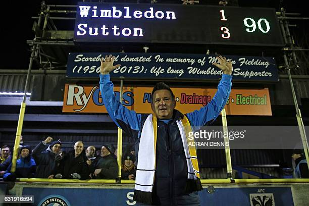Sutton United's English manager Paul Doswell poses for a photograph under the scoreboard as he celebrates their win after the English FA Cup third...