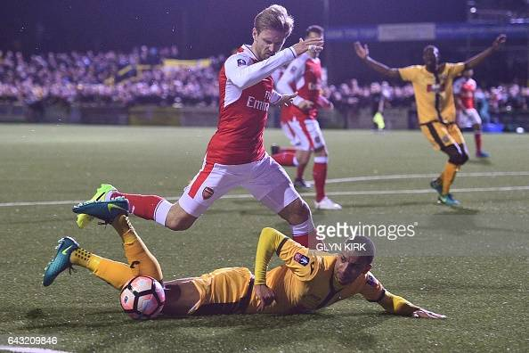 Sutton United's English midfielder Craig Eastmond falls to the floor after a challenge from Arsenal's Spanish defender Nacho Monreal during the...