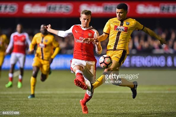 Sutton United's French striker Maxime Biamou vies with Arsenal's English defender Rob Holding during the English FA Cup fifth round football match...