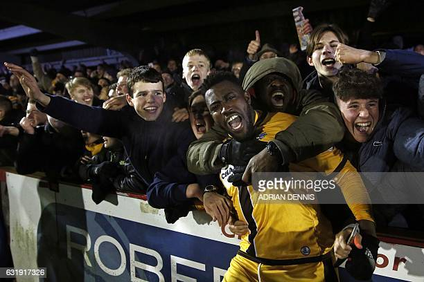 Sutton United's Ghanaian midfielder Bradley HudsonOdoi celebrates their win with supporters after the English FA Cup third round replay football...