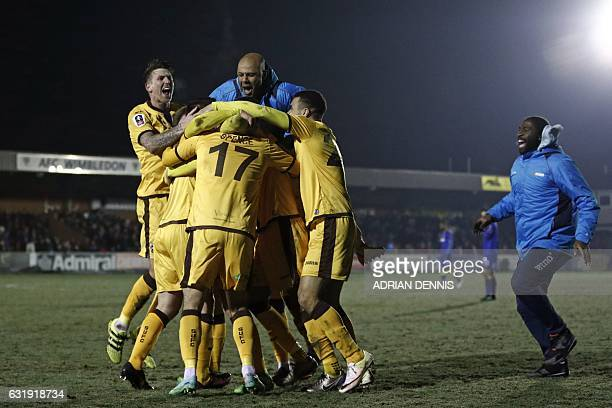 Sutton United's players celebrate on the pitch at the final whistle in the English FA Cup third round replay football match between AFC Wimbledon and...
