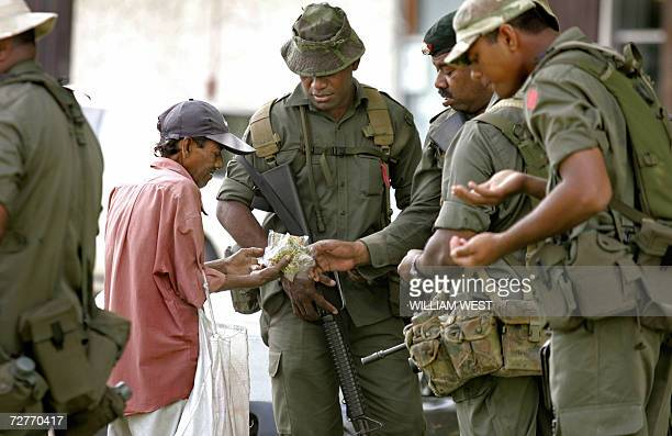 Soldiers buy a snack from a roadside trader as the army patrols the street after a coup by Fiji's military leader Voreqe Bainimarama in Suva 08...