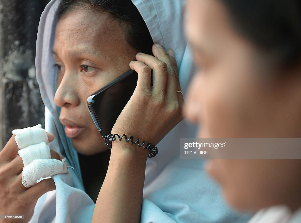 A suvivor (L) talks to a relative over a borrowed mobile phone outside the office of the ferry company in Cebu City, central Philippines on August 17, 2013 after a ferry collided with a cargo ship and sank on August 16. Stormy weather forced Philippine rescuers to suspend a search on August 17 for 171 people missing after a crowded ferry collided with a cargo ship and quickly sank, with 31 others confirmed dead. AFP PHOTO/TED ALJIBE