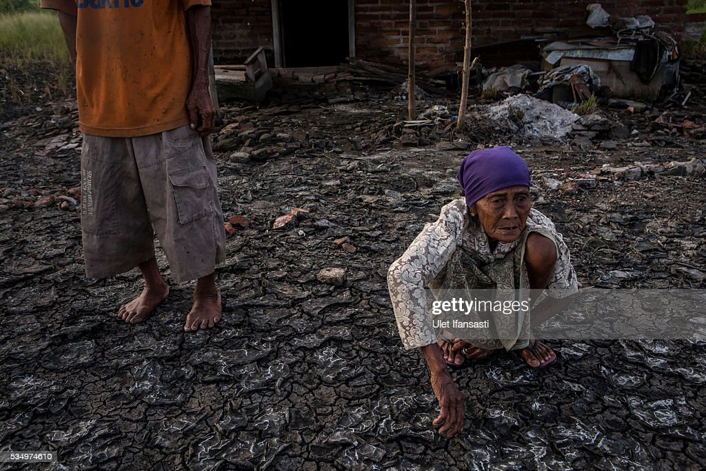 Suwadi (75) and his wife, Saniaka (80), stand behind their house which is affected by mudflow on May 27, 2016 in Sidoarjo, East Java, Indonesia. Residents of villages that were damaged by the Sidoarjo mudflow and residents received compensation, after almost ten years, from the Indonesian oil and gas company, PT Lapindo Brantas. The mudflow eruption is suspected to have been triggered by the drilling activities of oil and gas company, though they refute the claims, instead blaming a 6.3 magnitude earthquake that struck a neighboring city two days before the mudflow eruption. The earthquake struck Yogyakarta on May 27th, 2006, a city 150 miles west of a drill site in Sidoarjo, two days before the mudflow eruption. According to reports, twenty lives were lost and nearly 40,000 people displaced, with damages topping $2.7 billion. Ten years since the eruption, the mud geysers continue to spurt daily and high levels of heavy metals have been detected in nearby rivers.
