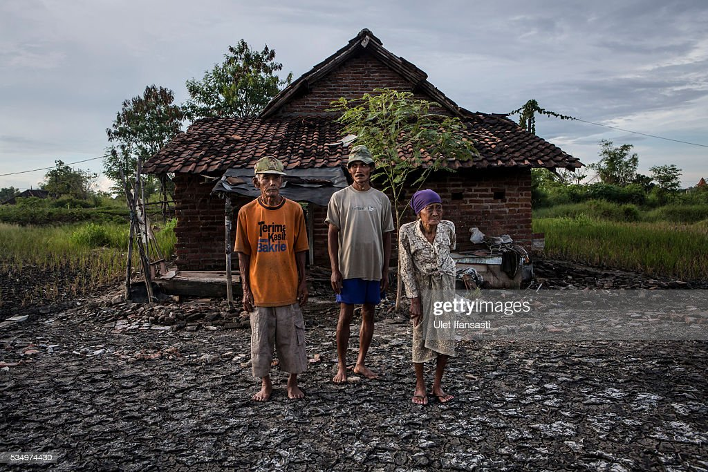 Suwadi (75), his wife, Saniaka (80), and their son Yono (C), stand behind their house which is affected by mudflow on May 27, 2016 in Sidoarjo, East Java, Indonesia. Residents of villages that were damaged by the Sidoarjo mudflow and residents received compensation, after almost ten years, from the Indonesian oil and gas company, PT Lapindo Brantas. The mudflow eruption is suspected to have been triggered by the drilling activities of oil and gas company, though they refute the claims, instead blaming a 6.3 magnitude earthquake that struck a neighboring city two days before the mudflow eruption. The earthquake struck Yogyakarta on May 27th, 2006, a city 150 miles west of a drill site in Sidoarjo, two days before the mudflow eruption. According to reports, twenty lives were lost and nearly 40,000 people displaced, with damages topping $2.7 billion. Ten years since the eruption, the mud geysers continue to spurt daily and high levels of heavy metals have been detected in nearby rivers.