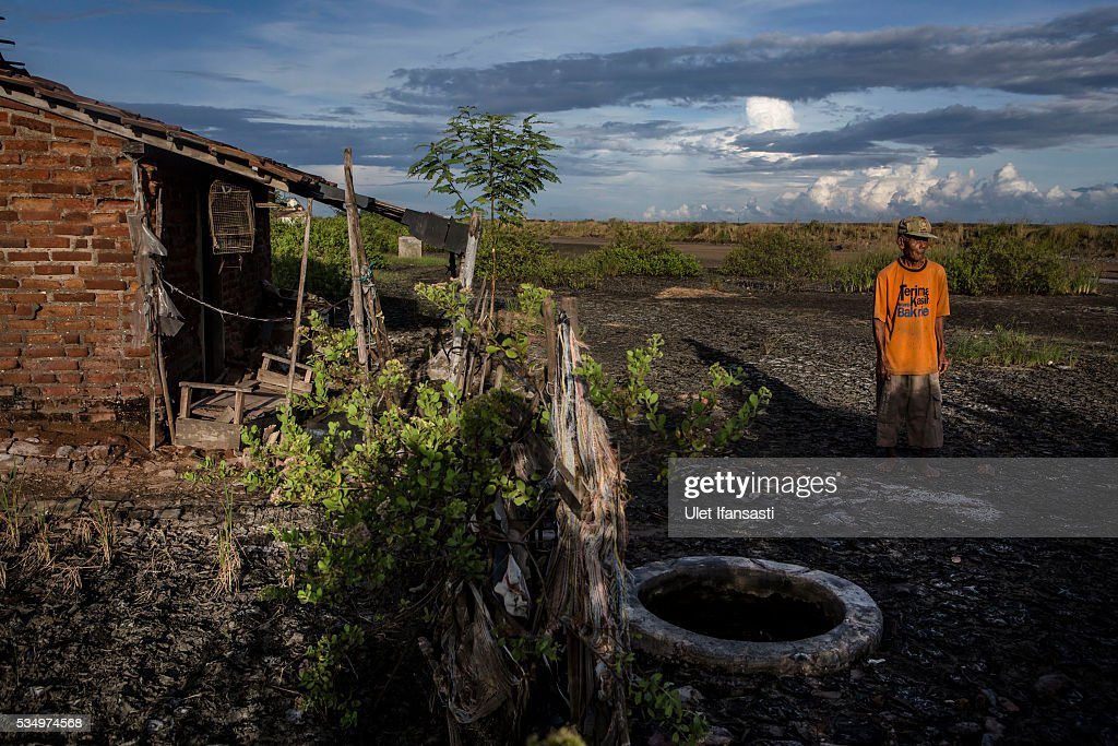 Suwadi (75), stands behind his house affected by mudflow on May 27, 2016 in Sidoarjo, East Java, Indonesia. Residents of villages that were damaged by the Sidoarjo mudflow and residents received compensation, after almost ten years, from the Indonesian oil and gas company, PT Lapindo Brantas. The mudflow eruption is suspected to have been triggered by the drilling activities of oil and gas company, though they refute the claims, instead blaming a 6.3 magnitude earthquake that struck a neighboring city two days before the mudflow eruption. The earthquake struck Yogyakarta on May 27th, 2006, a city 150 miles west of a drill site in Sidoarjo, two days before the mudflow eruption. According to reports, twenty lives were lost and nearly 40,000 people displaced, with damages topping $2.7 billion. Ten years since the eruption, the mud geysers continue to spurt daily and high levels of heavy metals have been detected in nearby rivers.