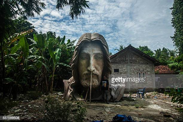 Suwarto with his work head Jesus Christ statue with a height of 9 meter in Bantul Yogyakarta Indonesia on June 1 2016 Suwarto can make craft realist...