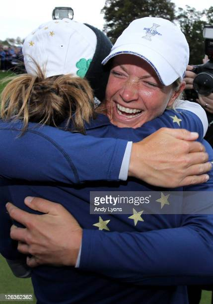 Suzann Pettersen of Europe celebrates her team's 1513 victory on the 18th green with Azahara Munoz during the singles matches on day three of the...
