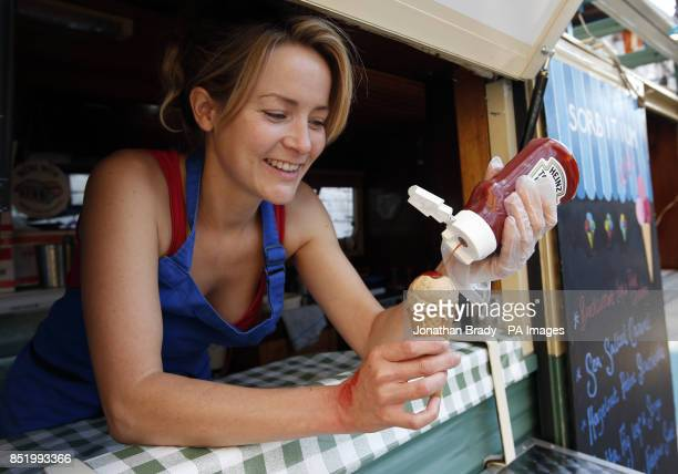 Suzanna Austin from Sorbitium pours ketchup over a cone containing her BBQ burger with candied bacon and dill gherkin ripple ice cream made...
