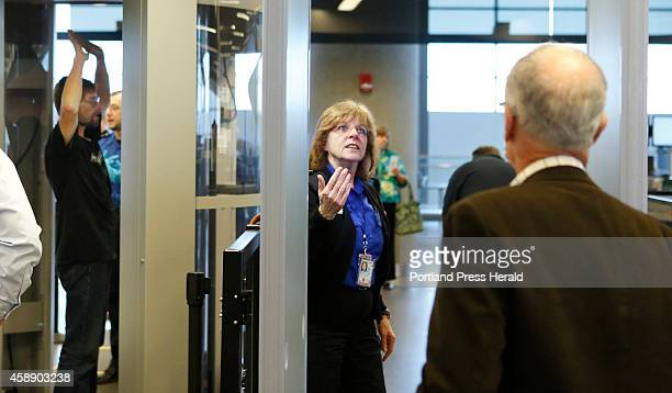 Suzanne Quintal a TSA officer motions for a man to walk through a metal detector in the security area at the Portland International Jetport on...