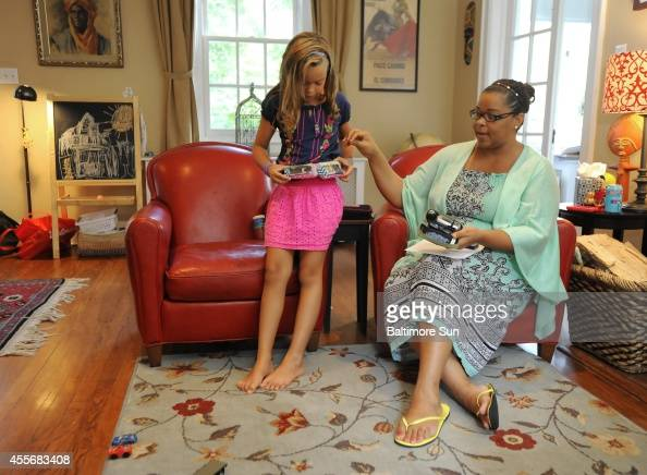 Suzanne Razaq right looks at her daughter Zara's Cheek's insulin pump and her glucose meter Aug 5 2014 in Baltimore Zara a 7yearold girl with Type I...