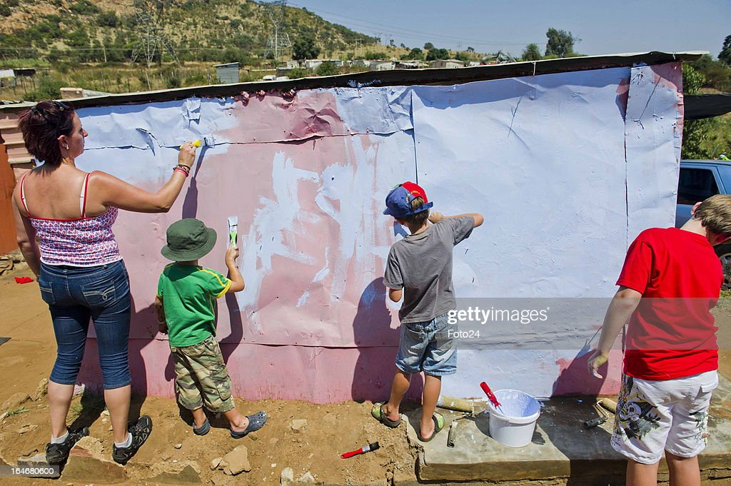 Suzanne Scott, Richardo Coetzer, John Alexander and Alex Blake paint a shack at the Alaska Informal settlement on March 24, 2013 in Mamelodi, South Africa. The Viva Foundation hosted the second Mams Art Festival at the informal settlement over the weekend. The art festival focuses on creating the world's first living art gallery by transforming shacks into art work.
