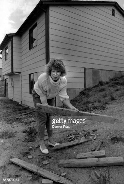 Suzi Hadley stands in the back yard of and holds a board with nails Credit The Denver Post