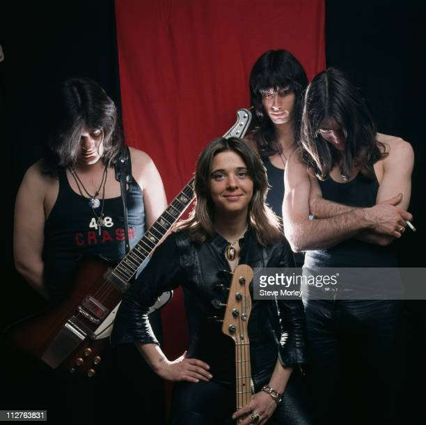 Suzi Quatro US singersongwriter with the other members of her band standing behind her their heads bowed circa 1978 Quatro is holding a bass guitar