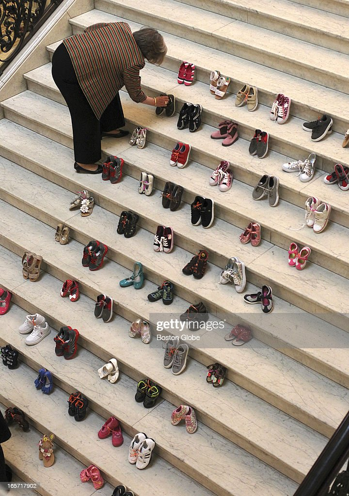 Suzin Bartley, executive director of the Children's Trust Fund works on the display of 69 pair of children's shoes on the Grand Staircase at the State House. Each pair represent the average number of children abused every day in Massachusetts.