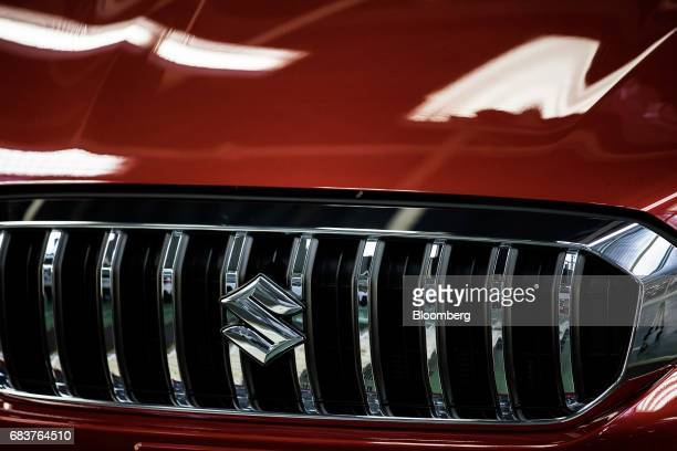 A Suzuki badge sits on the front grille of a Suzuki SX4 SCross Crossover automobile on the assembly line inside the Suzuki Motor Corp plant in...