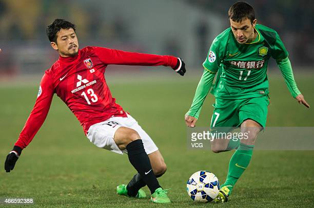 Suzuki Keita#13 Of Urawa Red Diamonds competes the ball against Pablo Batalla of Beijing Guo'an during the AFC Asian Champions League match between...