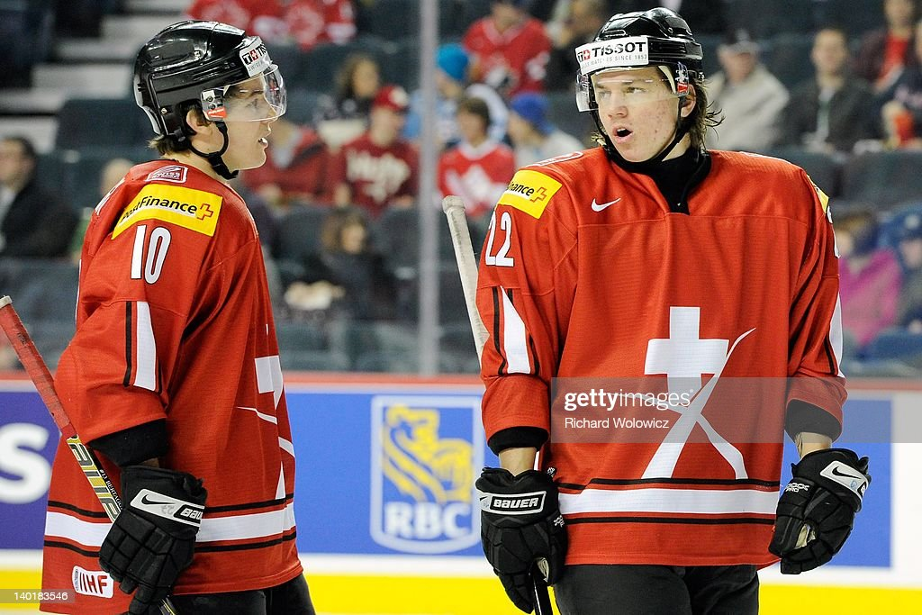 Sven Adrighetto #22 and Alessio Bertaggia #10 of Team Switzerland talk with play stopped during the 2012 World Junior Hockey Championship game against Team Denmark at the Saddledome on January 2, 2012 in Calgary, Alberta, Canada.