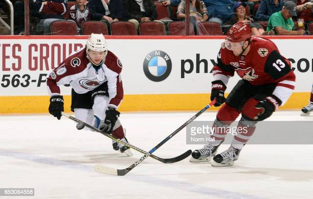Sven Andrighetto of the Colorado Avalanche and Peter Holland of the Arizona Coyotes skate for a loose puck during the first period at Gila River...