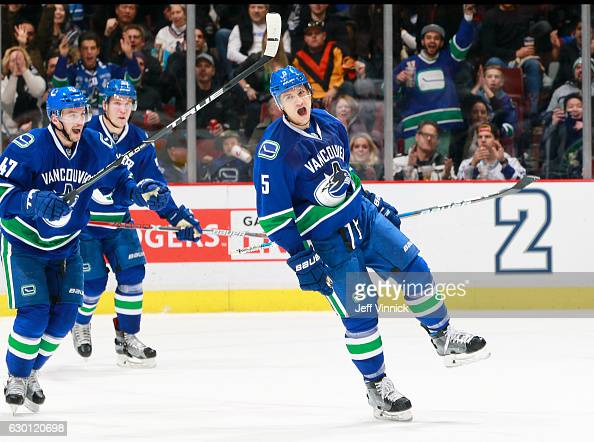 Sven Baertschi and Bo Horvat help Luca Sbisa of the Vancouver Canucks celebrate a goal against the Tampa Bay Lightning during their NHL game at...