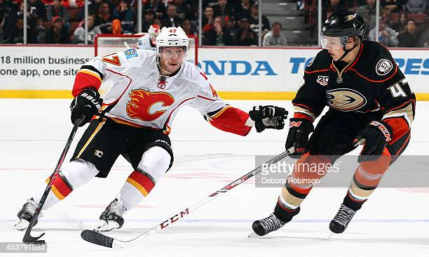 Sven Baertschi of the Calgary Flames handles the puck against Hampus Lindholm of the Anaheim Ducks on November 29 2013 at Honda Center in Anaheim...