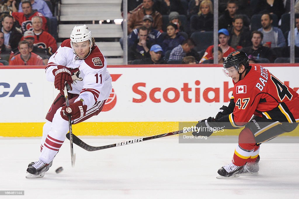 <a gi-track='captionPersonalityLinkClicked' href=/galleries/search?phrase=Sven+Baertschi&family=editorial&specificpeople=7832299 ng-click='$event.stopPropagation()'>Sven Baertschi</a> #47 of the Calgary Flames tries to check <a gi-track='captionPersonalityLinkClicked' href=/galleries/search?phrase=Martin+Hanzal&family=editorial&specificpeople=2109469 ng-click='$event.stopPropagation()'>Martin Hanzal</a> #11 of the Phoenix Coyotes during an NHL game at Scotiabank Saddledome on April 12, 2013 in Calgary, Alberta, Canada.
