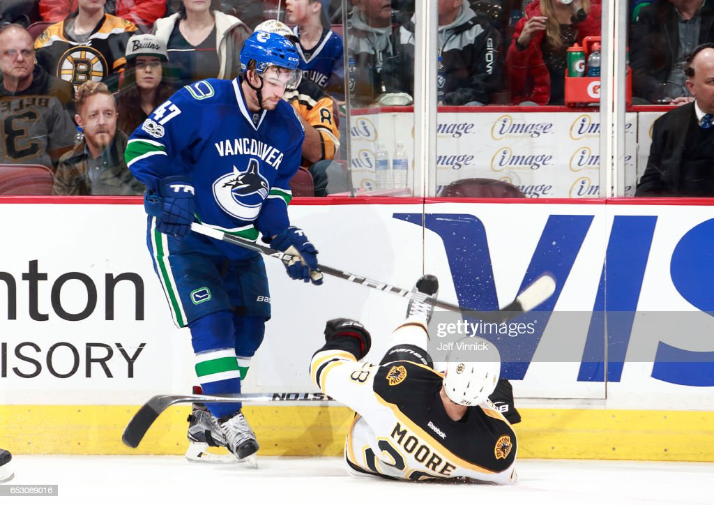 Sven Baertschi #47 of the Vancouver Canucks checks Dominic Moore #28 of the Boston Bruins during their NHL game at Rogers Arena March 13, 2017 in Vancouver, British Columbia, Canada. Boston won 6-3.