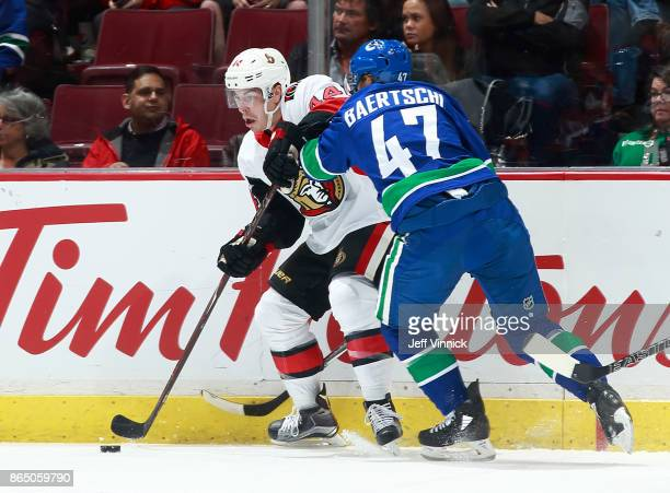 Sven Baertschi of the Vancouver Canucks checks JeanGabriel Pageau of the Ottawa Senators during their NHL game at Rogers Arena October 10 2017 in...