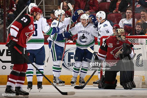 Sven Baertschi of the Vancouver Canucks is congratulated by Bo Horvat and Alexandre Burrows after scoring a goal against the Arizona Coyotes during...