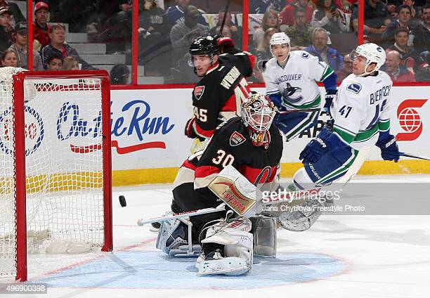 Sven Baertschi of the Vancouver Canucks scores a first period goal against Andrew Hammond of the Ottawa Senators as Chris Wideman of the Ottawa...