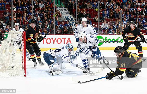 Sven Baertschi of the Vancouver Canucks scores on James Reimer of the Toronto Maple Leafs as he is checked by Roman Polak of the Maple Leafs during...
