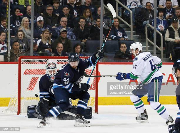 Sven Baertschi of the Vancouver Canucks watches as the puck gets past goaltender Michael Hutchinson of the Winnipeg Jets for a first period goal by...