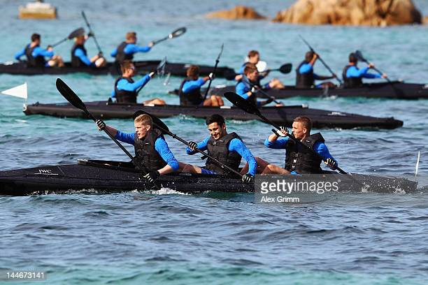 Sven Bender Ilkay Guendogan and Lukas Podolski compete during a boat race of the German national football team outside the team hotel 'Romazzino' on...