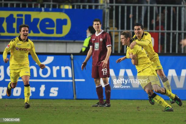 Sven Bender of Dortmund celebrates his team's first goal with team mates Nuri Sahin and Mario Goetze as Jiri Bilek of Kaiserslautern reacts during...