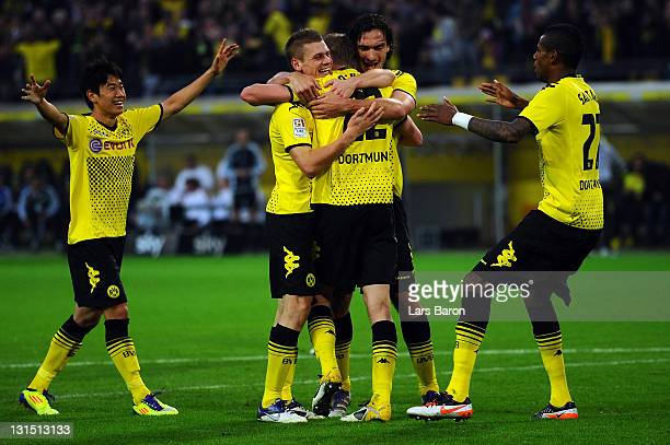Sven Bender of Dortmund celebrates with Shinji Kagawa and other team mates after scoring his teams thirg goal during the Bundesliga match between...