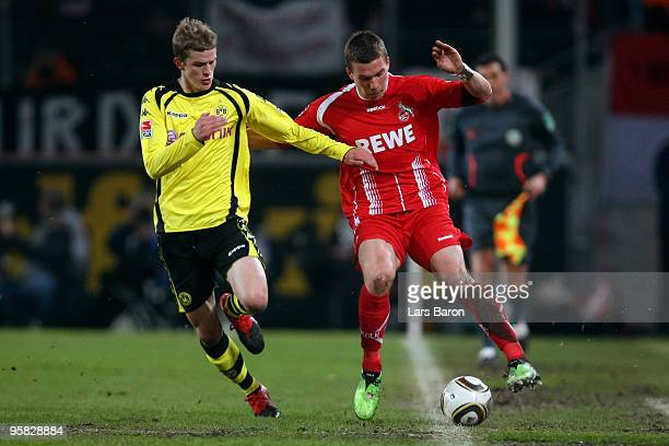 Sven Bender of Dortmund challenges Lukas Podolski of Koeln during the Bundesliga match between 1 FC Koeln and Borussia Dortmund at...