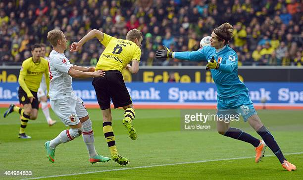 Sven Bender of Dortmund heads his teams first goal against Matthias Ostrzolek and goalkeeper Marwin Hitz of Augsburg during the Bundesliga match...