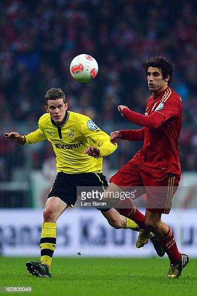 Sven Bender of Dortmund is challenged by Javier Martinez of Muenchen during the DFB cup quarter final match between Bayern Muenchen and Borussia...