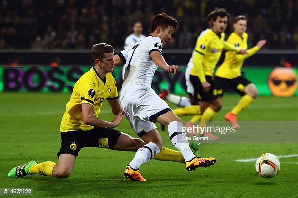 Sven Bender of Dortmund is challenged by Son HeungMin of Tottenham during the UEFA Europa League Round of 16 first leg match between Borussia...